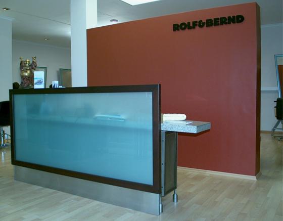 Counter mit farbiger Glasfront in einem Friseursalon. Dahinter eine frei- stehende, beidseitig beplankte Ständerwerkskonstruktion als Sichtschutz- wand. Die Oberfläche wurde nach Kundenwunsch gestaltet.