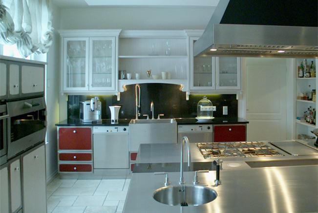 In der Küchenzeile an der Stirnwand korrespondieren die Fronten der außen positionier- ten Unterschränke mit der Front der großen Insel (1). Die Oberschränke mit Glastüren sowie das Regal greifen mit den Kranzprofilen Elemente des Landhaus-Stils auf.