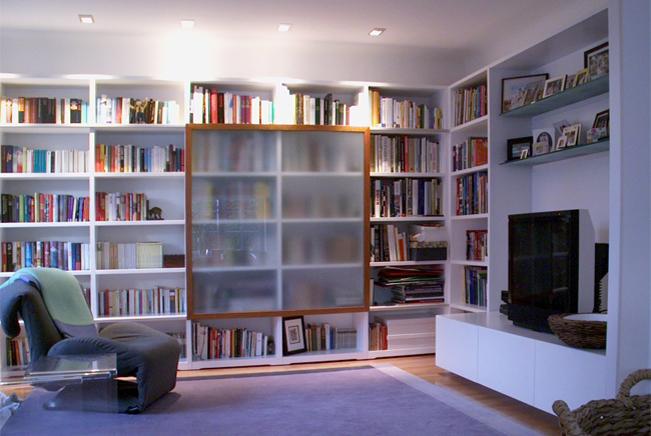 Das Bücherregal aus lackiertem MdF reicht von Wand zu Wand. Einen interessanten Akzent setzt die Kulissenschiebetür aus Kirschbaumholz mit satiniertem Sicherheitsglas.