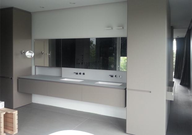 Auf der Rückseite des begehbaren Schranks (7) befindet sich das Badezimmer. Der Waschtisch mit wandbündig eingebautem Spiegelschrank wird von Hochschränken flankiert. Handwerkliche Präzisionsarbeit sind die durchlaufenden Griffnuten. Das Bad lässt sich mit einer Schiebetür schließen.